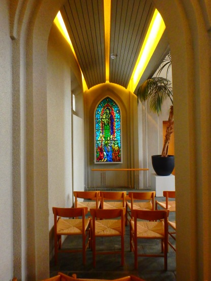 The white interior is punctuated with bright stained glass windows